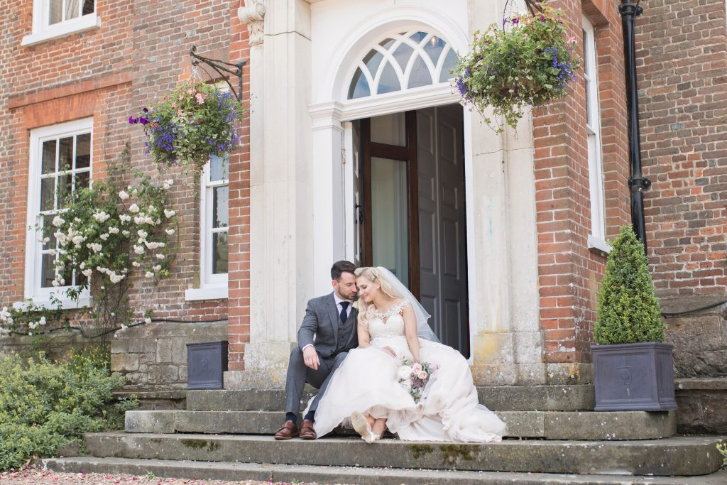 bride and groom on steps at chilston park