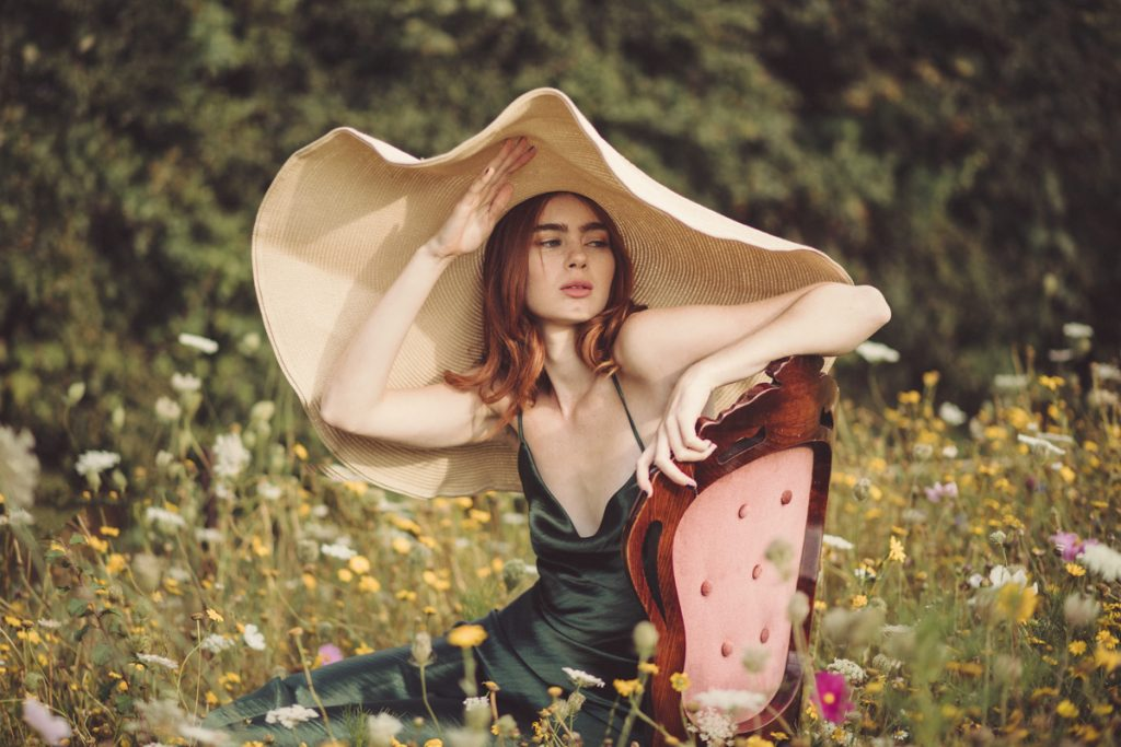 model with oversized hat in meadow
