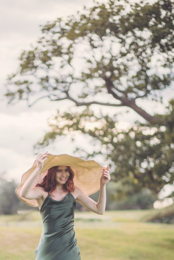 fun photo of red head model with oversized hat