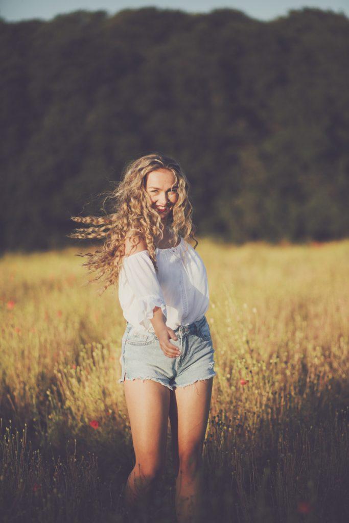 pretty girl in poppy field at golden hour