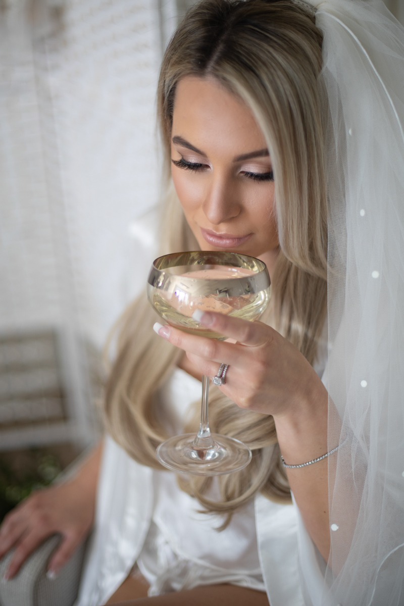 bride drinking champagne at preparations