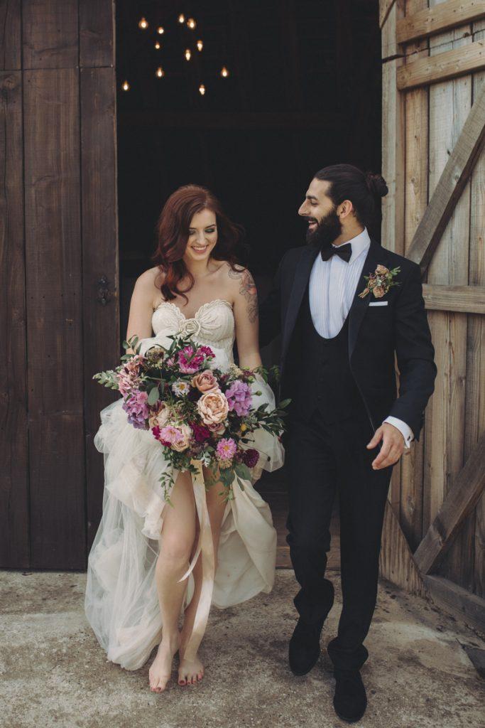 barefoot bride leaving barn wedding