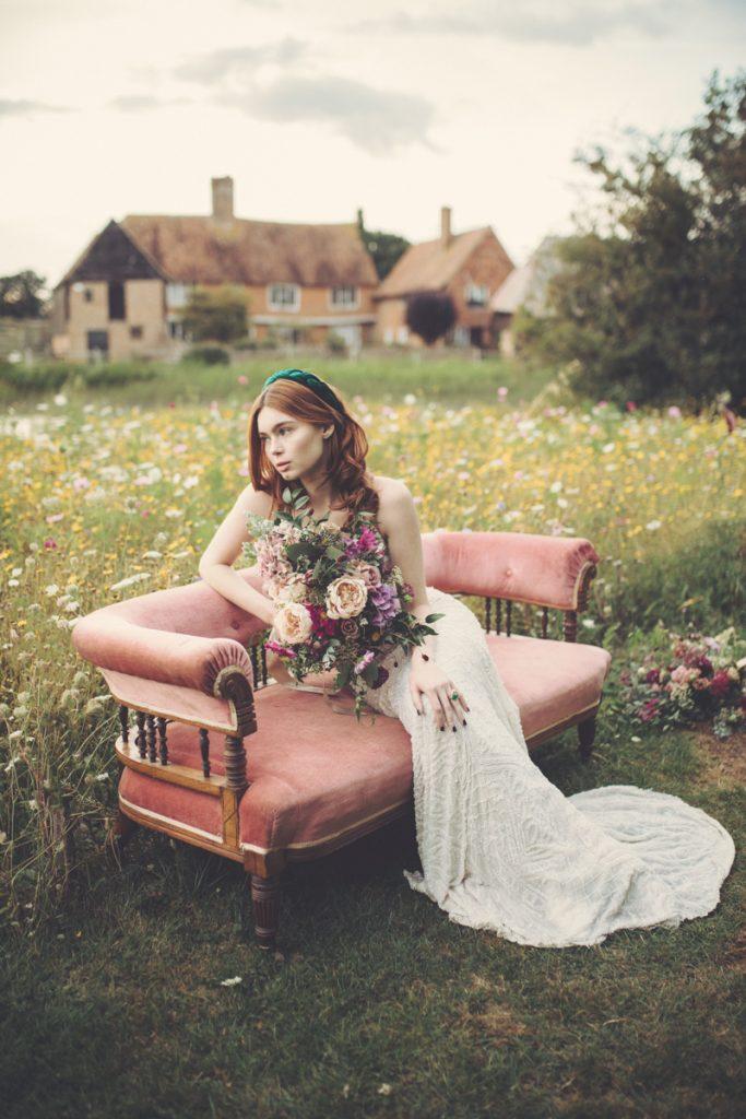 bride on velvet sofa in meadow