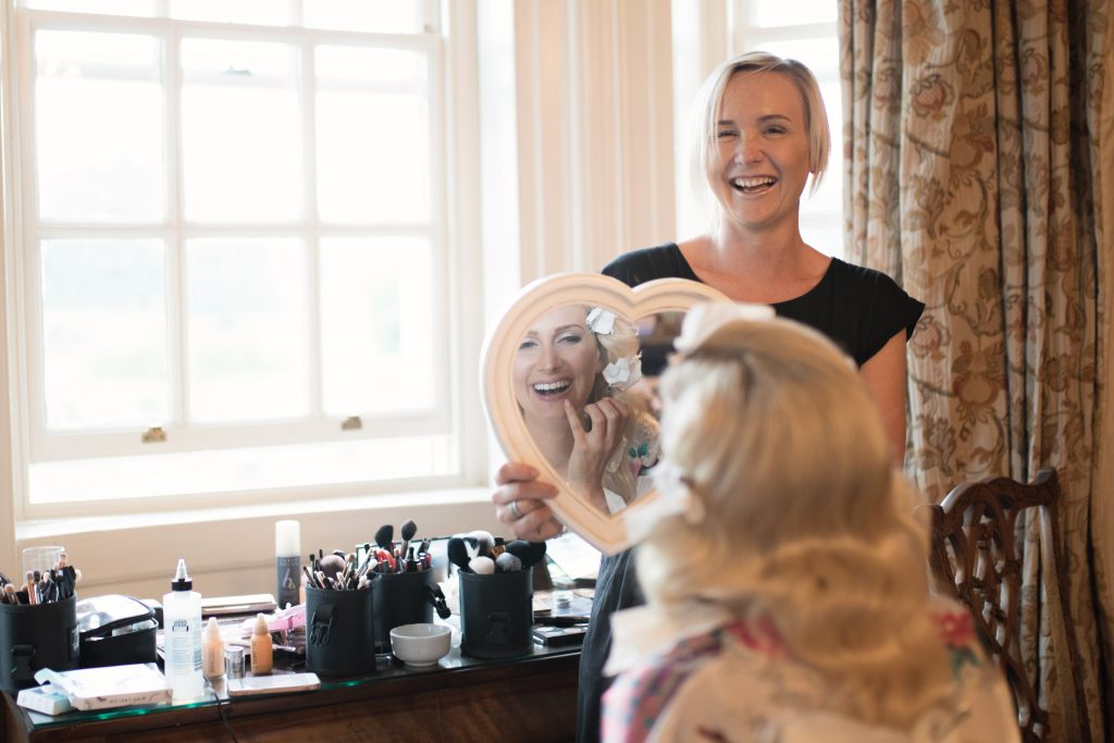 bride laughing with makeup artist