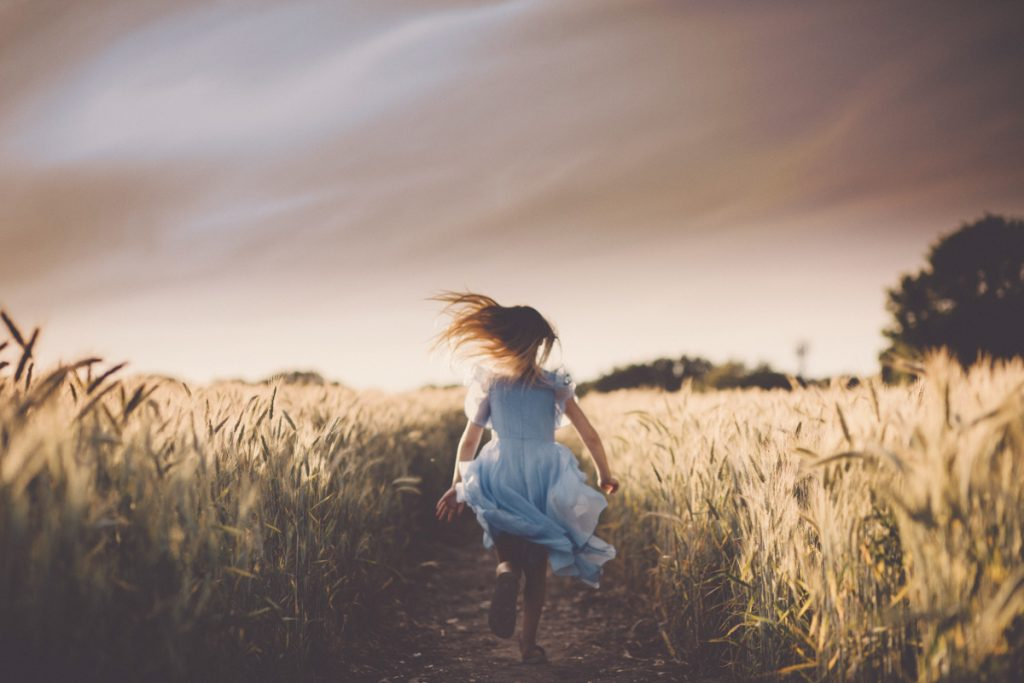 girl running in wheat field