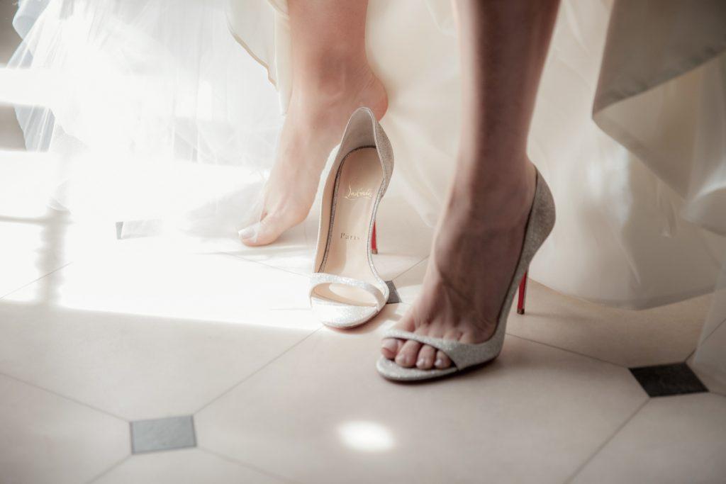 bride putting on louboutin shoe